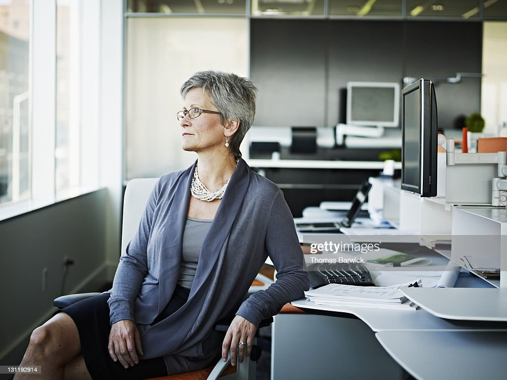 Businesswoman sitting at workstation looking out : Stock Photo