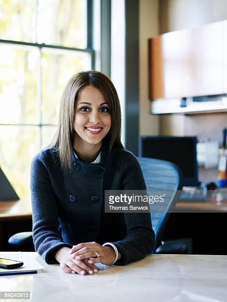 Businesswoman sitting behind desk, smiling