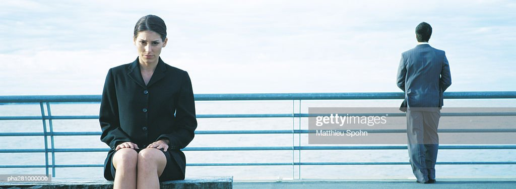 Businesswoman sitting, businessman standing at railing in background, panoramic : Stockfoto