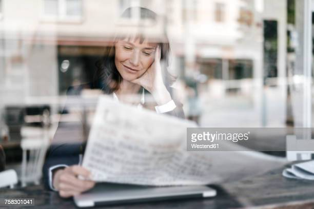 Businesswoman sitting cafe, reading newspaper