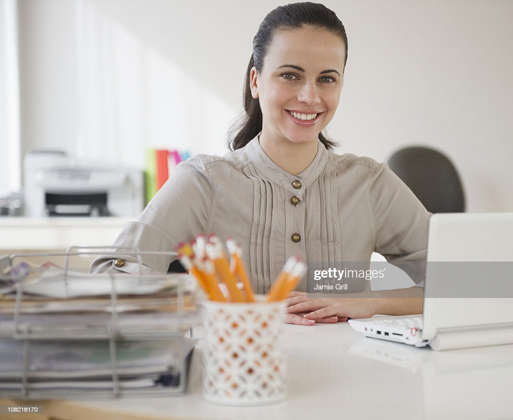 Businesswoman sitting confidently at desk : Stock Photo
