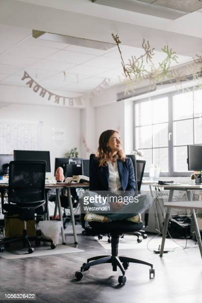 businesswoman sitting cross-legged on an office chair - office chair stock pictures, royalty-free photos & images