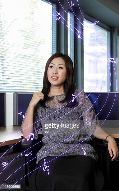 Businesswoman sitting down on chair in office