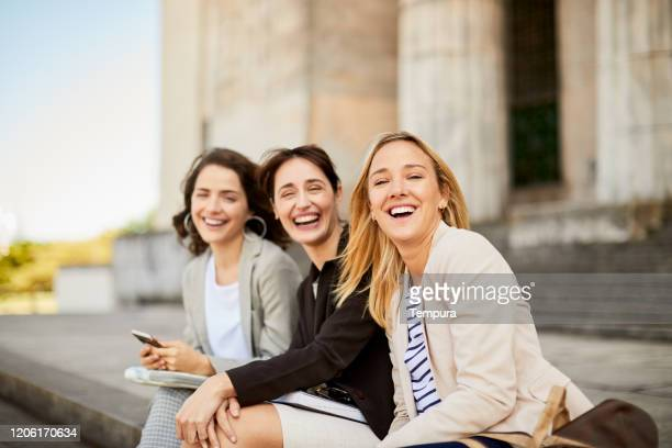 businesswoman sitting down outdoors and looking at camera. - universidad stock pictures, royalty-free photos & images