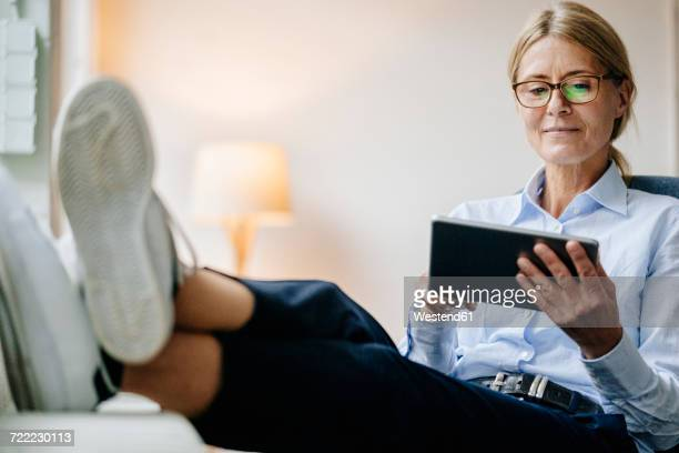 Businesswoman sitting down using tablet