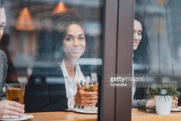 Geschäftsfrau, sitzen in einem Café und Tee zu trinken, beim Betrachten der Kameras