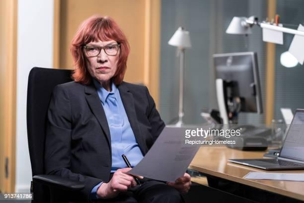 Eine Geschäftsfrau sitzt in ihrem Stuhl und hält Stift und Papier