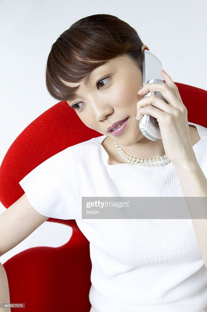 Businesswoman Sitting in a Chair and Using a Mobile Phone : Stock Photo