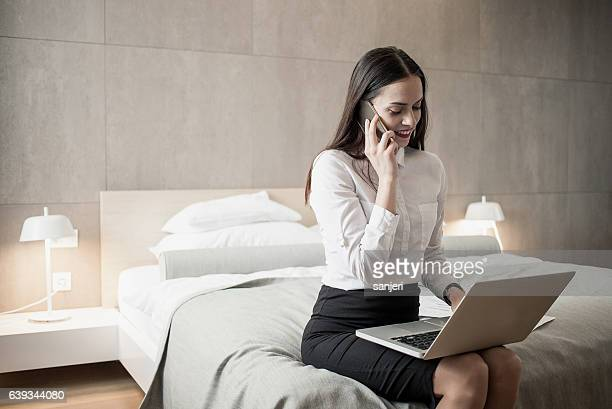 Businesswoman Sitting in a Hotel Room Using Laptop and Phone