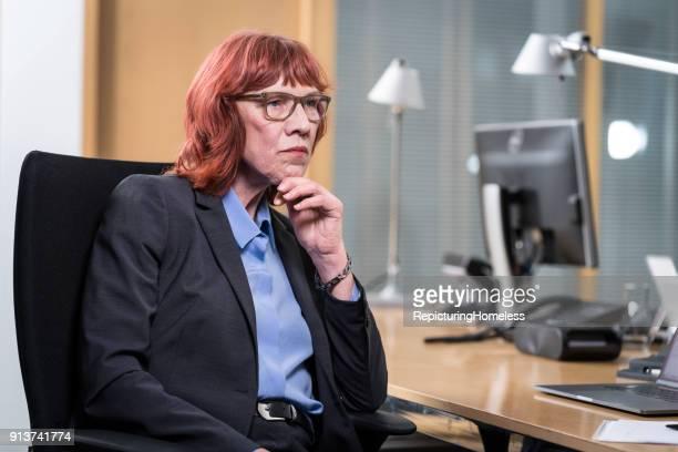 Eine Geschäftsfrau sitzt in ihrem Büro und denkt nach