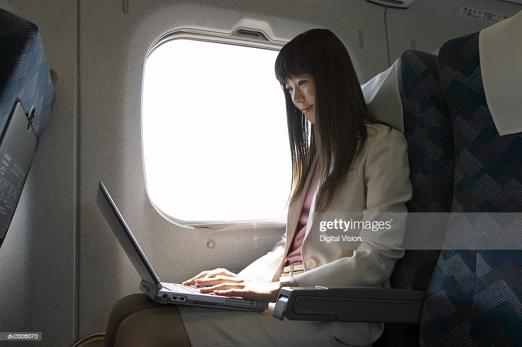Businesswoman Sitting in a Passenger Train and Using a Laptop : Stock Photo