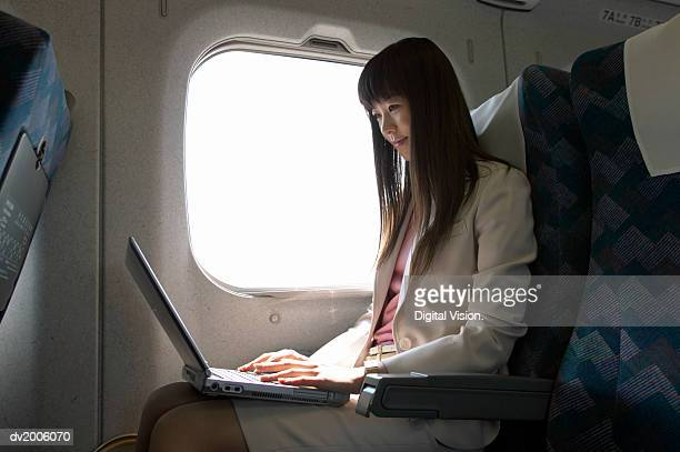 Businesswoman Sitting in a Passenger Train and Using a Laptop