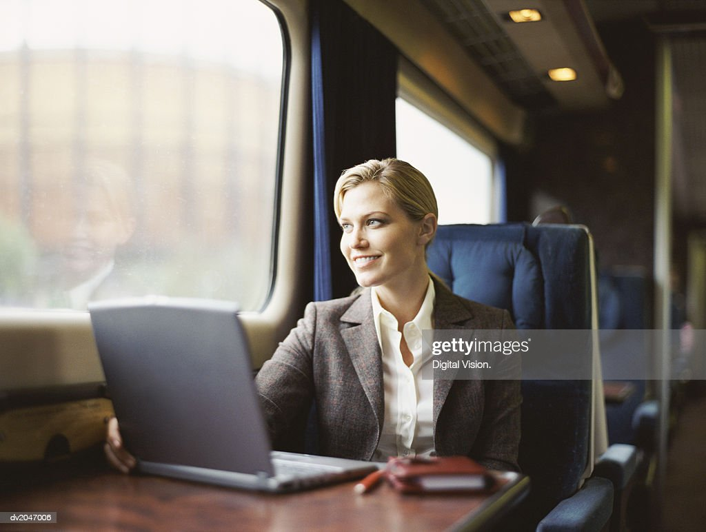 Businesswoman Sitting in a Train With a Laptop on a Table : Stock Photo