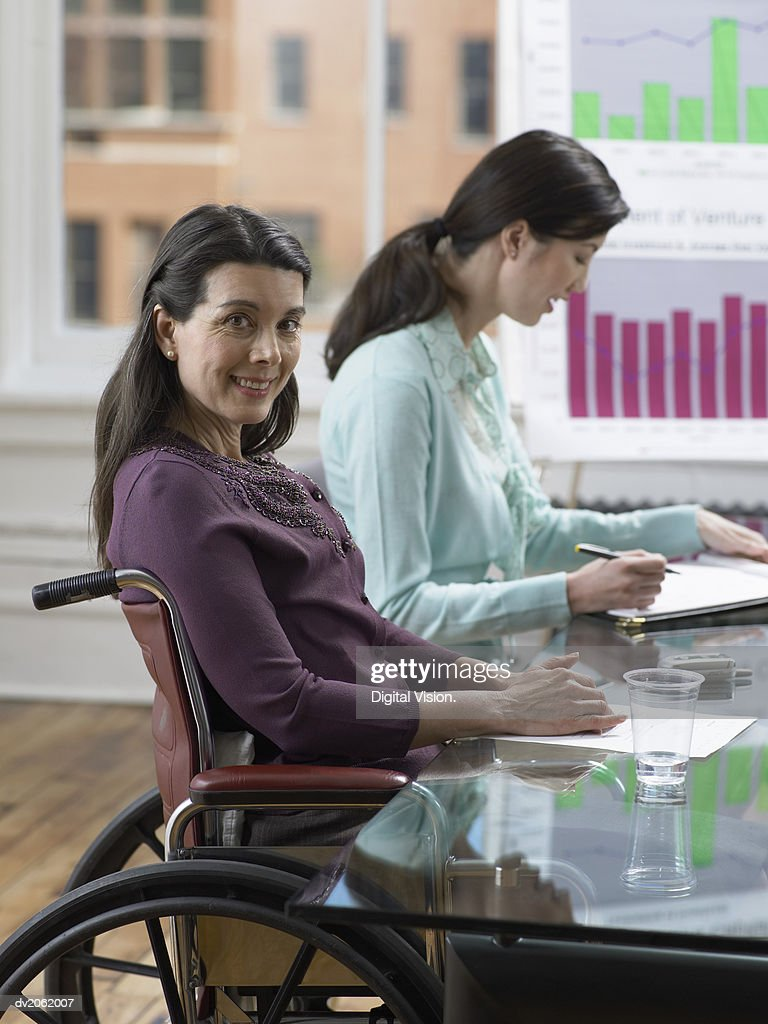 Businesswoman Sitting in a Wheelchair at a Conference Room Table : Stock Photo