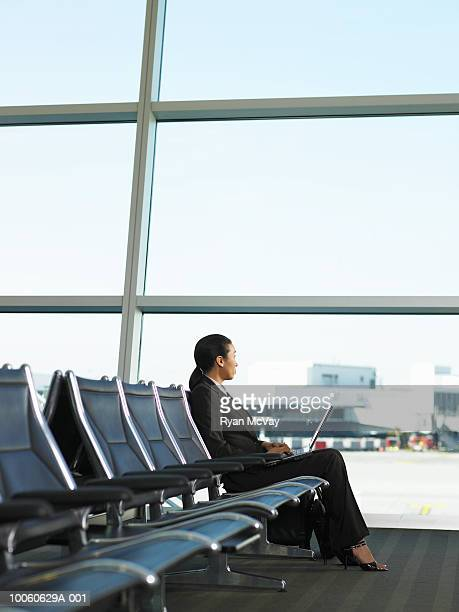 businesswoman sitting in airport using laptop, side view - transportation building type of building stock photos and pictures
