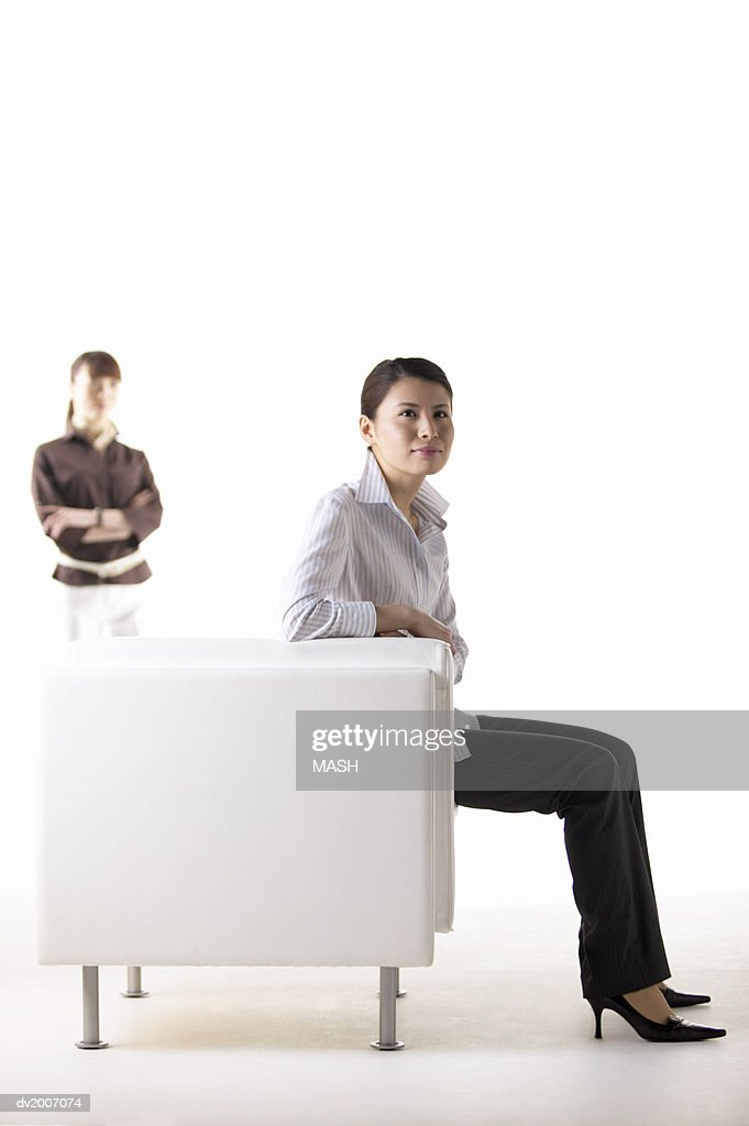Businesswoman Sitting in an Armchair With a Colleague With Arms Crossed in the Background : Stock Photo