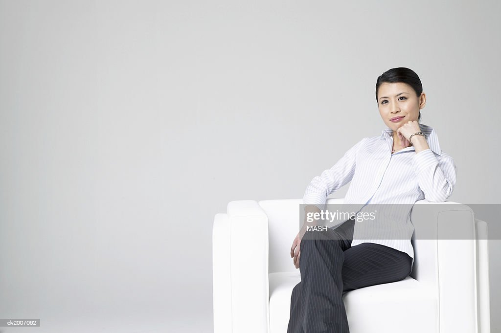 Businesswoman Sitting in an Armchair With Her Hand on Her Chin : Stock Photo