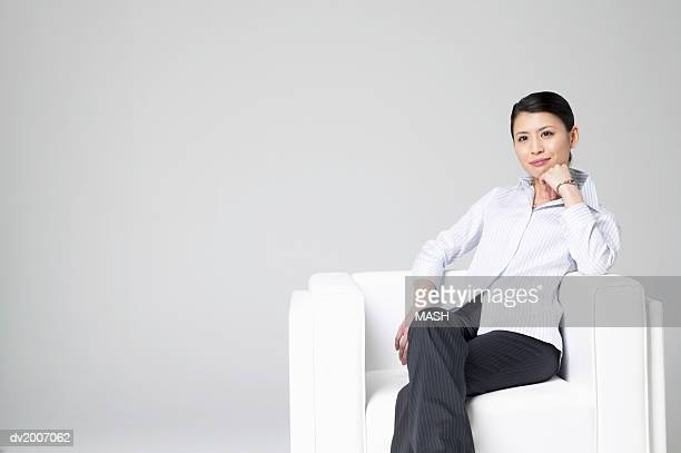 Businesswoman Sitting in an Armchair With Her Hand on Her Chin