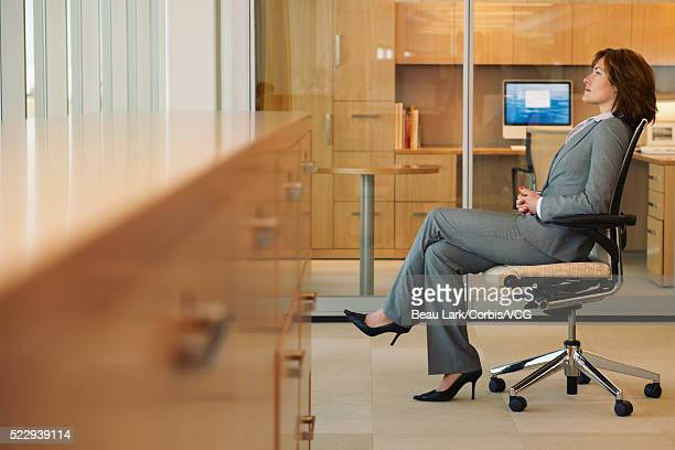 businesswoman sitting in an office - pant suit stock pictures, royalty-free photos & images