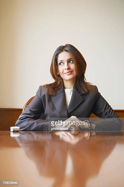 Businesswoman sitting in an office with her hands clasped
