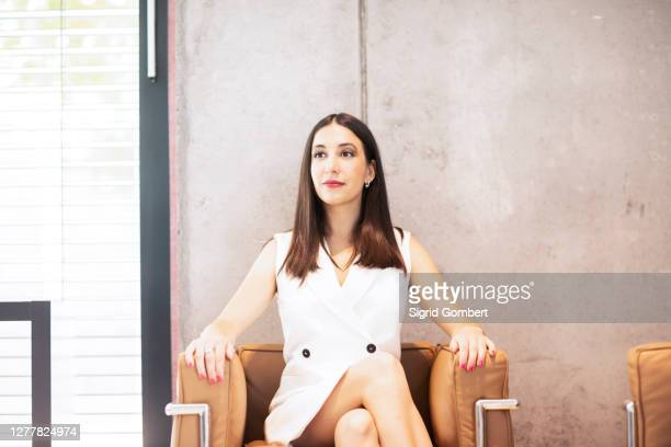 businesswoman sitting in armchair, smiling - sigrid gombert stock pictures, royalty-free photos & images