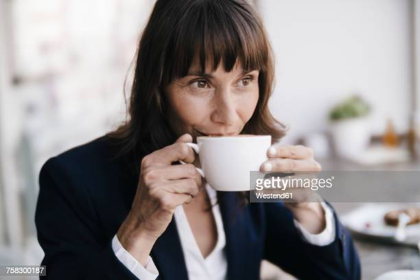 businesswoman sitting in cafe, drinking coffee - kaffee oder teepause stock-fotos und bilder