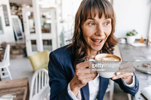 Businesswoman sitting in cafe, drinking coffee