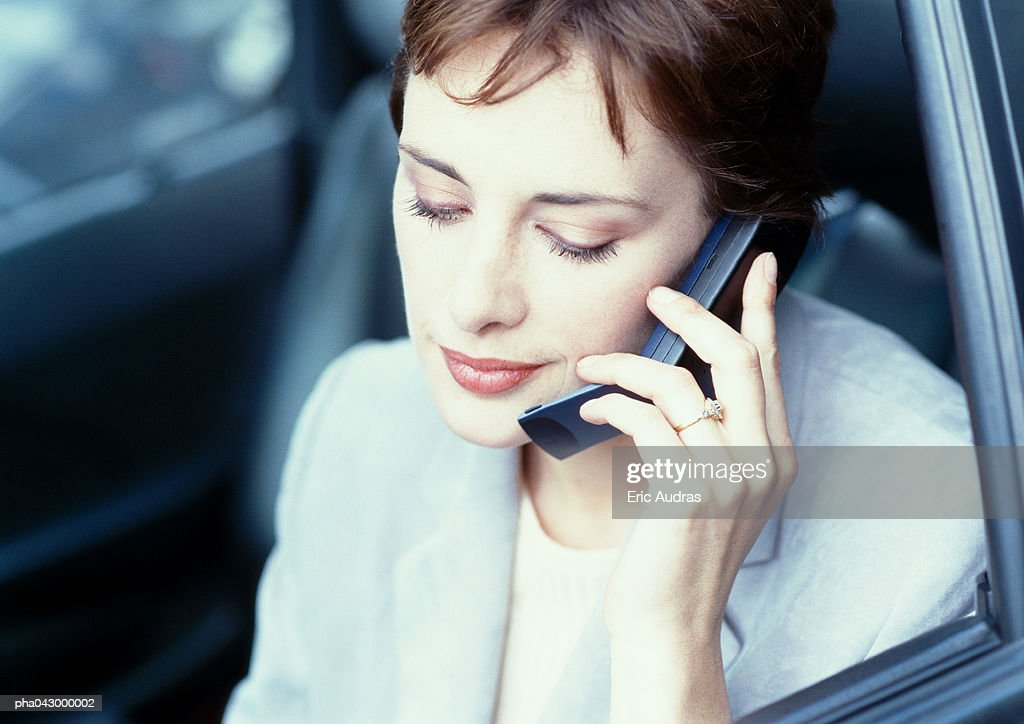 Businesswoman sitting in car, using cell phone : Stockfoto