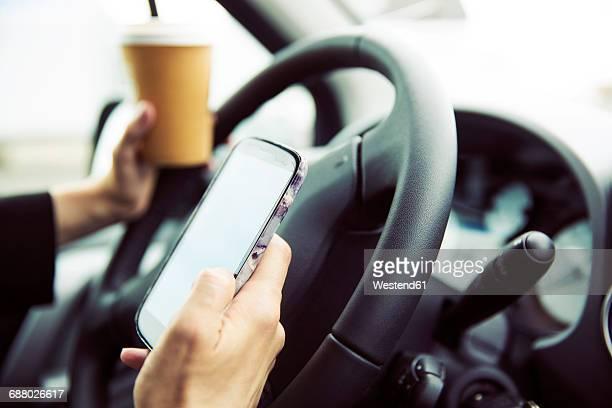 Businesswoman sitting in car, using smart phone