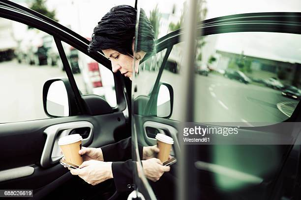 Businesswoman sitting in car, using smart phone