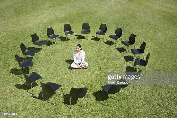 businesswoman sitting in circle of office chairs in field - surrounding stock pictures, royalty-free photos & images