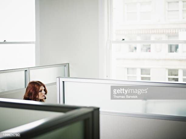 Businesswoman sitting in cubicle in office