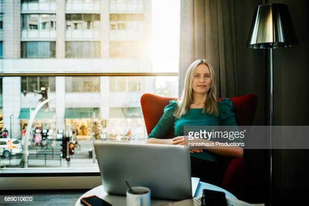 businesswoman sitting in front of laptop in hotel room - frau bluse durchsichtig stock-fotos und bilder