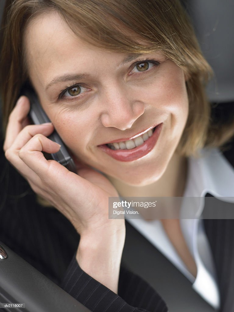 Businesswoman Sitting in Her Car Using a Mobile Phone : Stock Photo