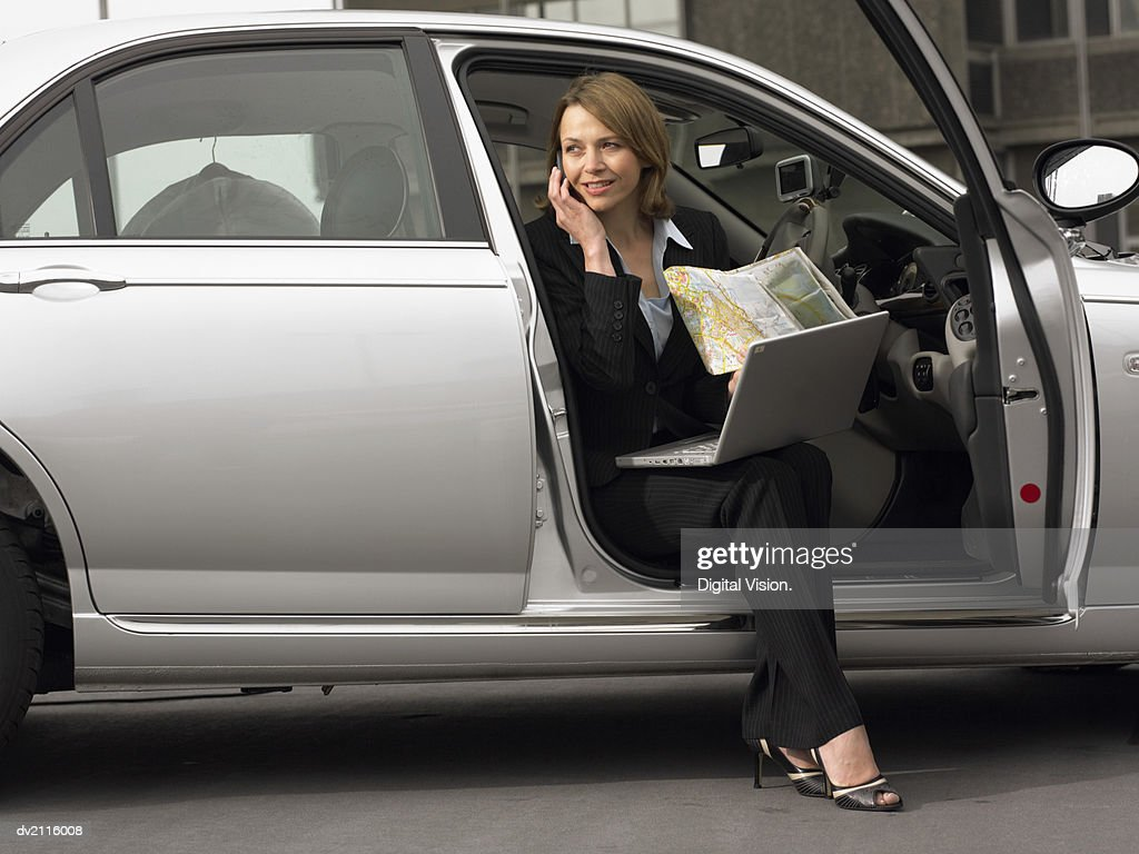 Businesswoman Sitting in Her Car Using a Mobile Phone With a Laptop and a Map : Stock Photo