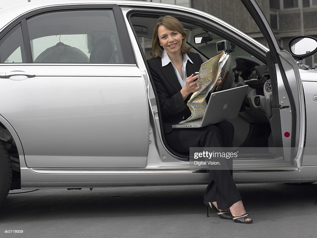 Businesswoman Sitting in Her Car With a Laptop and a Map : Stock Photo
