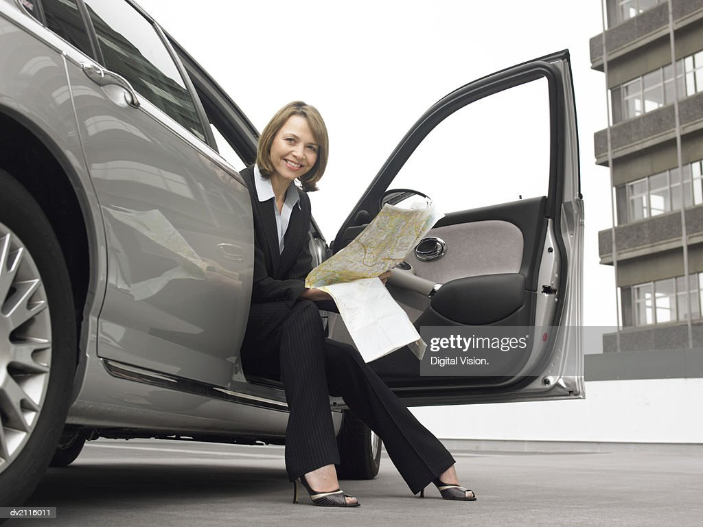 Businesswoman Sitting in Her Car With a Map : Stock Photo