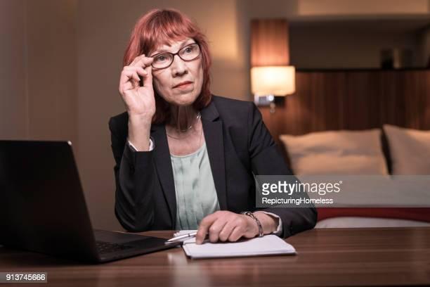 Porträt einer Geschäftsfrau die fokussiert in ihrem Hotelzimmer sitzt