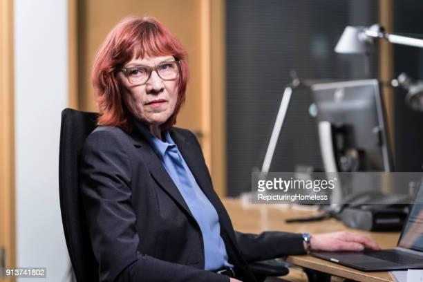eine geschäftsfrau sitzt in ihrem büro und schaut in die kamera - repicturing homeless stock-fotos und bilder