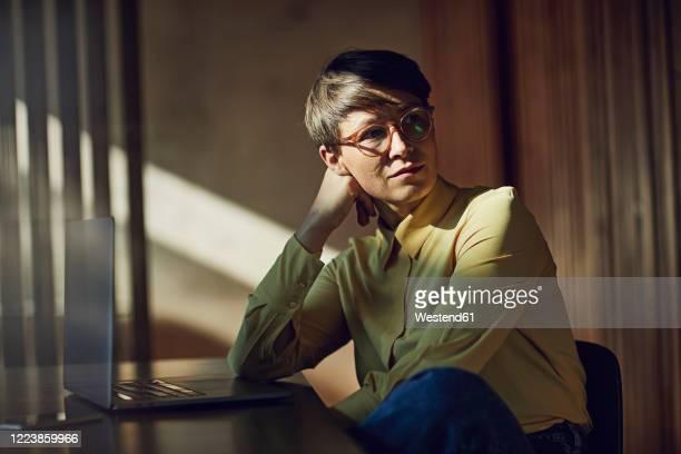 businesswoman sitting in her sustainable office, portrait - einfaches leben stock-fotos und bilder