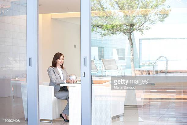 Businesswoman sitting in hotel lobby holding sphere