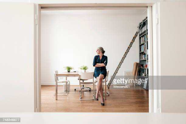 businesswoman sitting in modern office - grey dress stock pictures, royalty-free photos & images