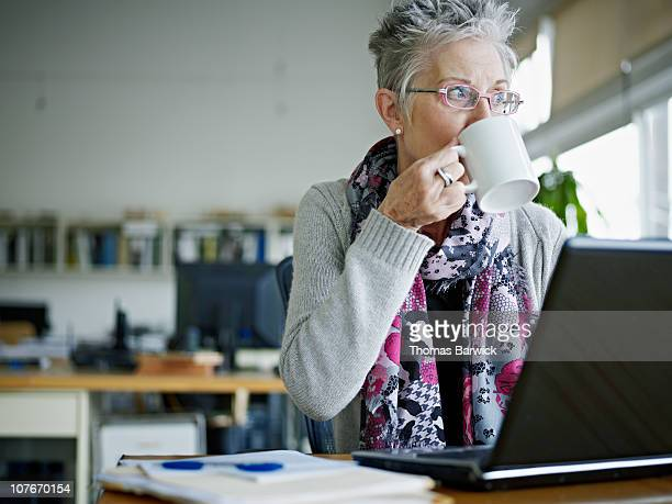 Businesswoman sitting in office drinking coffee