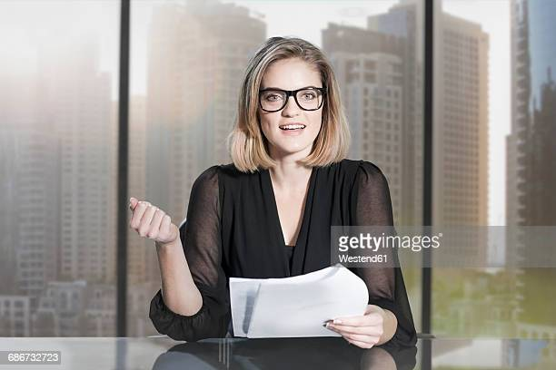Businesswoman sitting in office, looking at camera