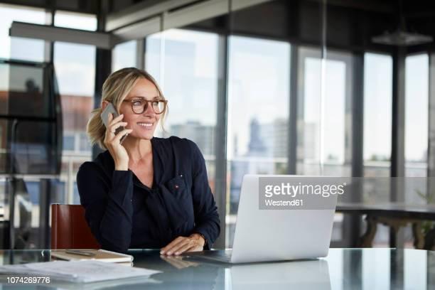 businesswoman sitting in office, talking on the phone - mulher de negócios imagens e fotografias de stock