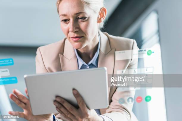 Businesswoman sitting in office, using digital tablet