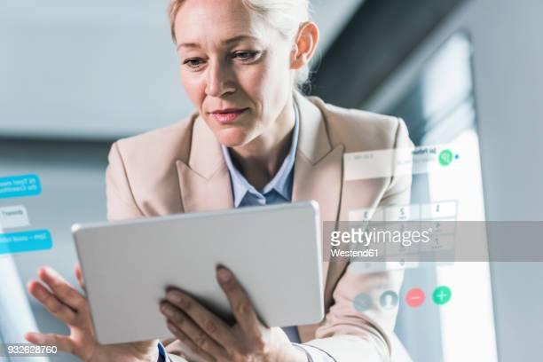 businesswoman sitting in office, using digital tablet - kontrolle stock-fotos und bilder