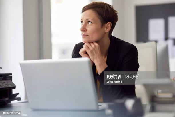 businesswoman sitting in office, using laptop - solo una donna di età media foto e immagini stock