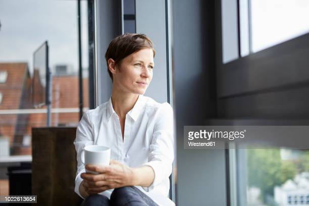 businesswoman sitting in office with cup of coffee looking out of window - bluse stock-fotos und bilder