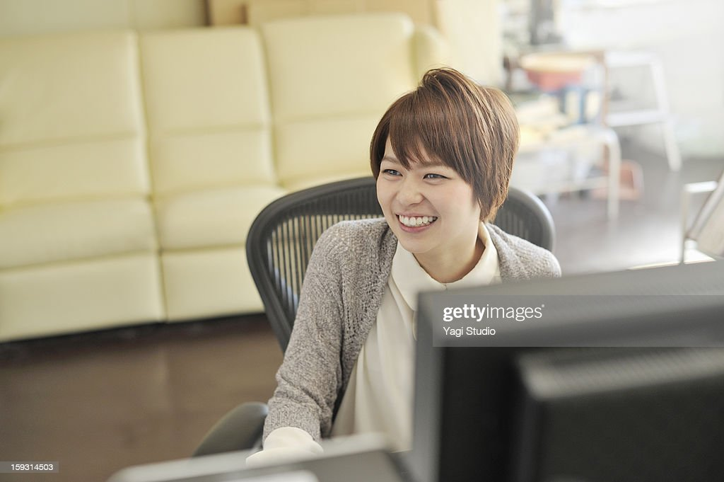 Businesswoman sitting in office,smiling : Stock Photo